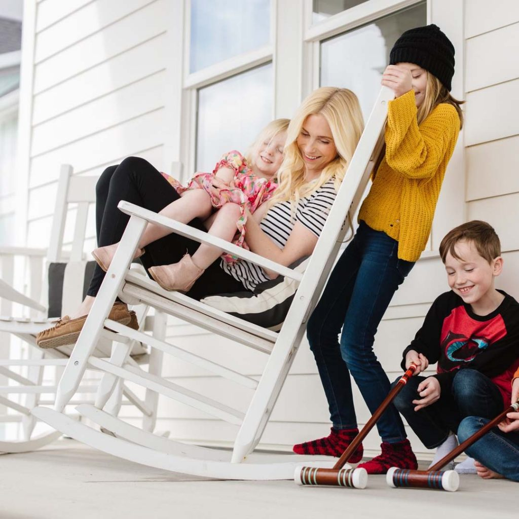 Mother laughs with her three children while sitting in a rocking chair | South Jordan, Utah.