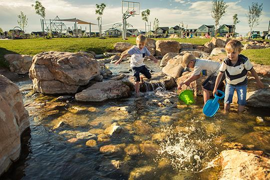 Kids playing in the brook at Brookside Park & Pool at Daybreak Utah