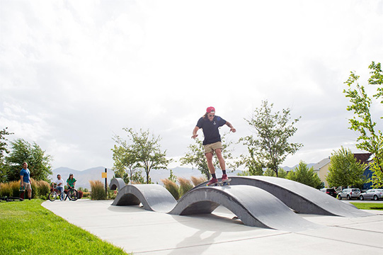 Boy skateboarding over Daybreak's skateable art installation at Eastlake Commons